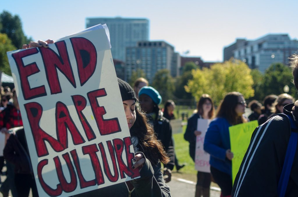 "A protest on a college campus with many young people gathered and holding signs. In the foreground, a person with wavy, long dark hair and a toque is holding a sign that says ""End Rape Culture."""