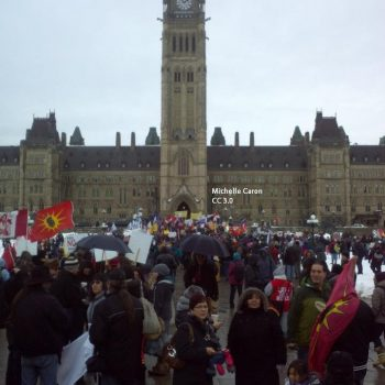 "a crowd stands in front of the canaidan parlimant building in ottawa. there are signs present that show the logo for ""idle no more"""