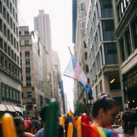 individuals stand ina crowded street between tall brick buildings. there are rainbow and transgender flags waving