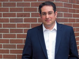 Image of Seth Klein standing against a brick wall