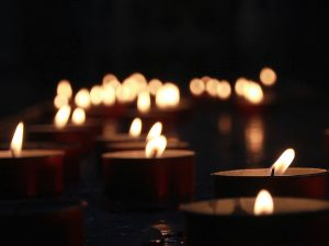 Image of many lit candles glowing in the dark