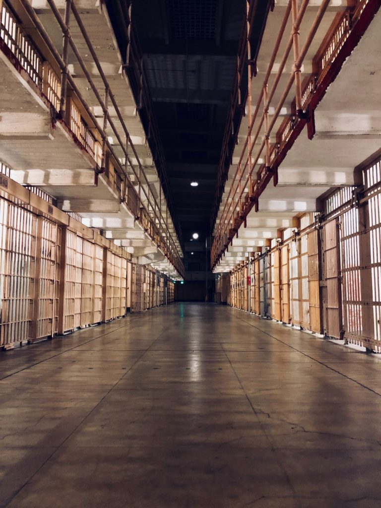 Photo of an empty prison hallway with cells on each side