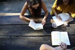 Photo of three people gathered at a table outside with notebooks and books working