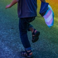 The lower part0 of a child (viewed from the back) running on a road carrying a trans flag with pink, blue and white stripes. There is a projection of rainbow-coloured light on the road.