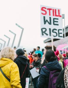 "Photo of a group of people outside showing their backs and one person holding a sign that says ""still we rise"""