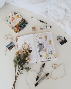 Photo of art supplies, journal and dried plants on a bed