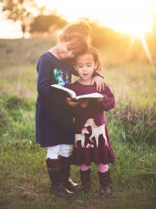 Photo of two little girls standing outside reading a book together