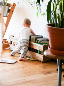 Photo of a baby standing at a book box pulling books out