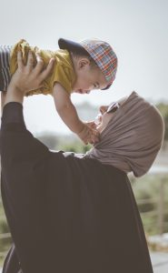 Photo of a woman wearing a hijab holding up a smiling baby in a baseball cap