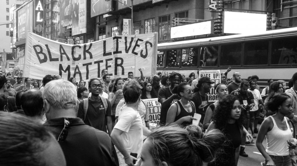 "Photo of rally walking down a city street and a large banner that says ""Black Lives Matter"" is centred"
