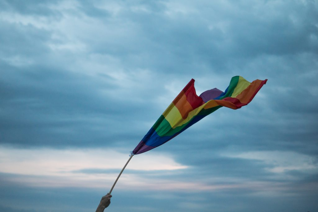 Photo of hand holding a rainbow flag in the air with the blue sky and clouds visible