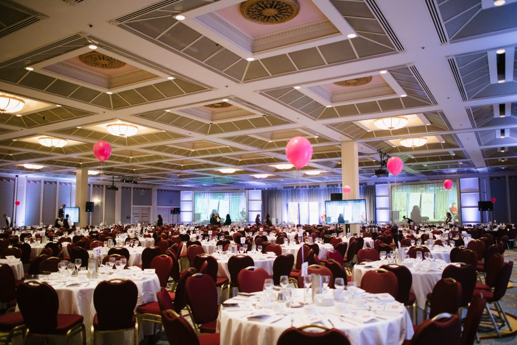 a photo of a banquet hall filled with circular tables awaiting attendees