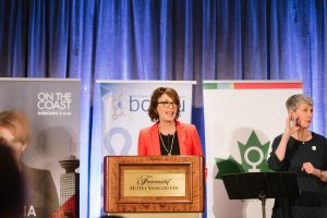 an individual stands at a podium speaking into a microphone. another individual (a sign language interpreter) is standing at the right of the photo. in the background are banners for cbc, the bcgeu, and west coast leaf