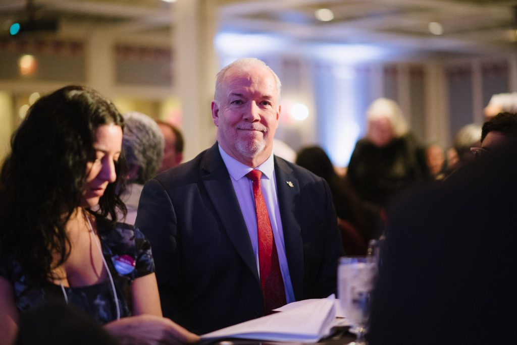 premier john horgan seated with fellow attendees at an event
