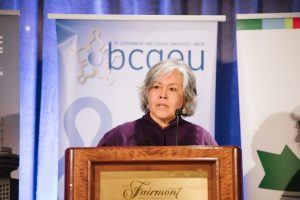 an individual stands in front of a podium speaking into a microphone. a banner for bcgeu is displayed behind the speaker