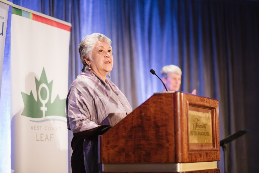 an individual stands at a podium speaking into a microphone. one other indivudal is out of focus in the background. a west coast leaf banner is displayed behind the speaker