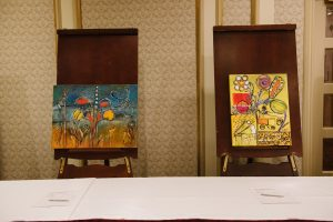 two pieces of colourful artwork is displayed on wooden easels in front of a table