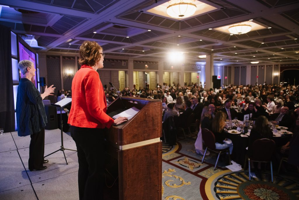 rear view of an individual stands at a podium and speaks into the microphone. a sign language interpreter stands on their left. the view is looking out into the event attendees