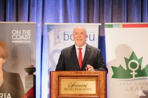premier john horgan stands at a podium speaking into a microphone. in the background are banners for bcgeu, west coast leaf, and the cbc