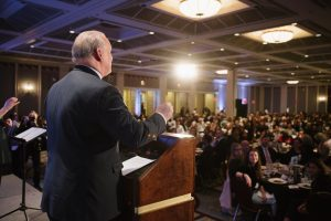 rear view of an individual stands at a podium and speaks into the microphone. the view is looking out into the event attendees