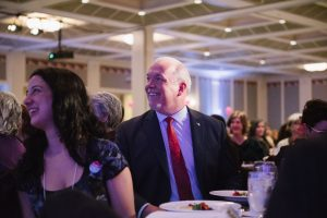 the central figure of the photo is premier john horgan along with other event attendees at the table.