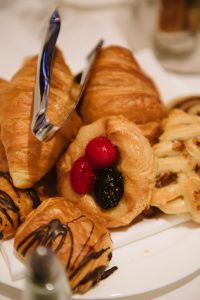 a close up of danishes and other breakfast treats topped with chocloate and fruit