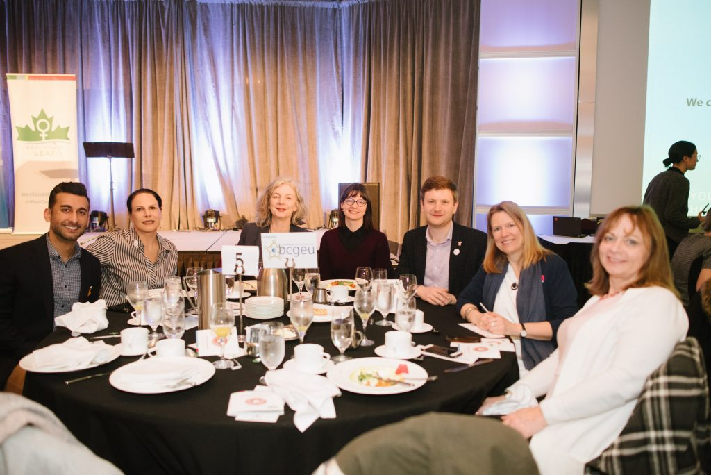 seven individuals sit around a circular table at an event. the central sign displays the bcgeu logo. a west coast leaf banner is in the background.
