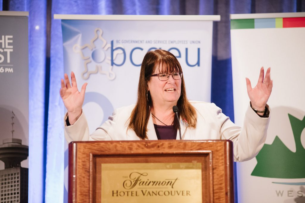 woman stands in front of podium from fairmont hotel vancuver, speaking into a microphone. in the background are bcgeu and west coast leaf banners