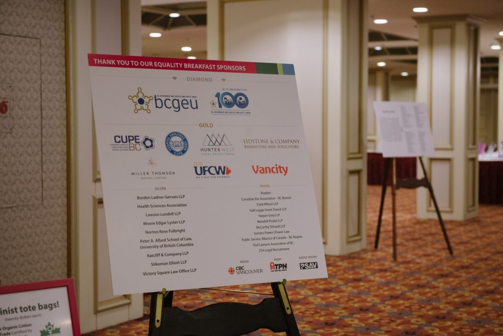 a banner is displayed on an easel bearing the names of event sponsors. most readable are bcgeu, cupe bc, ufcw, and vancity, though many other names and organisations are present