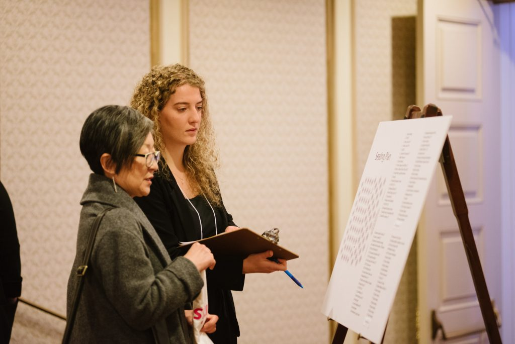 two individuals read information displayed on an easel. one carries a clipboard