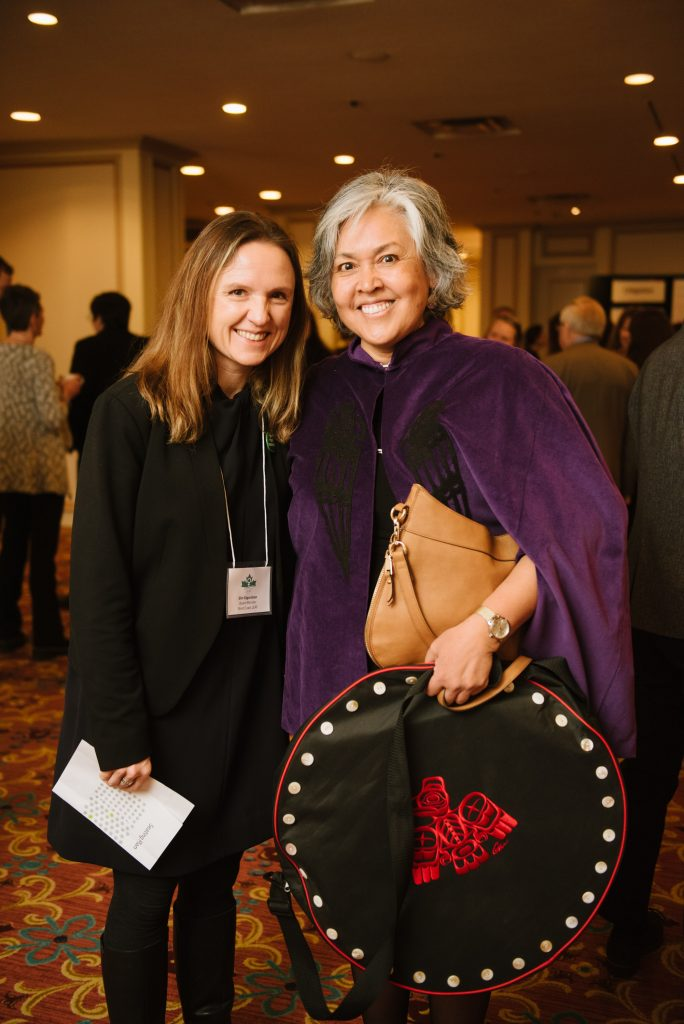 two individuals attending an event stand together, one carries a drum case designed in the pattern of a button blanket