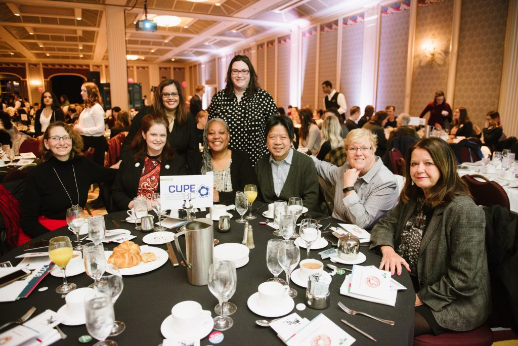 six individuals are seated together at a circular table during an event. two individual stand behind them. the sign on their table bears the name and logo for CUPE. in the background are fellow attendees within a banquet hall