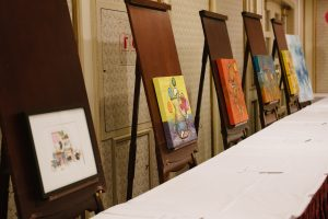 6 pieces of colourful artwork are displayed in front of a table