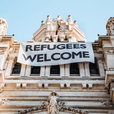 "Photo of a building in Spain with a large white banner that reads ""REFUGEES WELCOME"" in all caps and black writing"