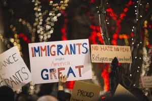 Photo from a protests where you can see people holding signs above their heads. Signs read immigrants make America great and no hate/no fear