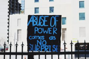 "Photo of a protest sign that reads ""abuse of power comes as no surprise"" on top of a fence"