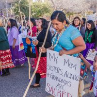 """Photo of a group of Indigenous women and children in traditional clothing walking in a march. A woman in a blue shirt with a walking stick, holds a sign that reads """"my Moms, sisters, Aunties and Grandmas are Sacred"""" A little boy is holding on to the sign."""