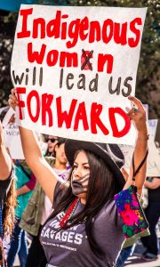"Photo of an Indigenous woman with a black painted handprint across her mouth holding a sign that reads ""Indigenous womxn will lead us forward."" In the background you can see other people behind holding signs in the crowd."