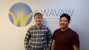 Photo of two people standing against a white wall that has the WAVAW logo and WAVAW rape crisis centre written on it. The person on the left is wearing a plaid shirt and the person on the right is wearing a black shirt. They are smiling at the camera