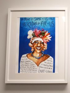 "Photo of a drawing in a white frame. The drawing is of Marsha P Johnson and written above here in the blue sky is ""No pride for some of us without liberation for all of us."""