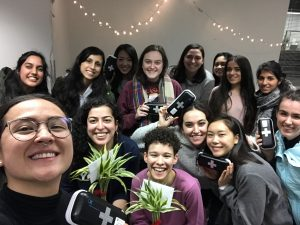 A selfie photo of a person taking the photo holding plants and behind the person is a large group of people holding naloxone kits