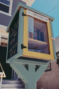 "Photo of a ""free little library"" stand outside with a house and blue sky in the background"