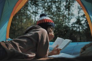 Photo of a person wearing a toque lying down on their stomach reading in a tent with trees and blue sky in the background.