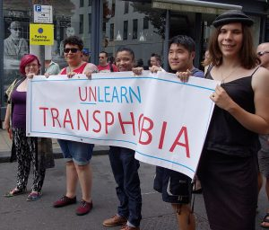 "Photo of a group of people holding a banner that reads ""Unlearn Transphobia"""