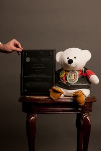 A photo of Spirit Bear sitting on a stool next to a leather book. A human hand is propping the book up in the photo.