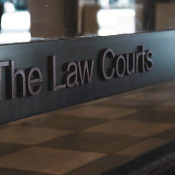 "A sign on a window that says ""The Law Courts."" A tile floor is visible through the window beneath the sign."