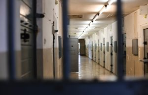 A photo through prison cell bars. You can see down the hallway to more cells. The hallway is empty.
