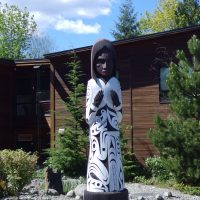 Photo of a welcome pole in front of Tillicum Lelum Friendship Centre. Behind is an office building.