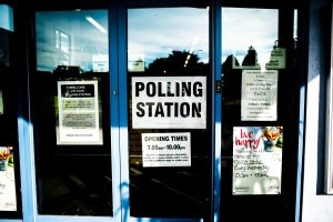 "Photo of a glass door with a sign on it that reads, ""POLLING STATION."""