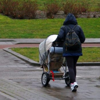 Person in a raincoat and jeans, pushing a stroller, viewed from the back